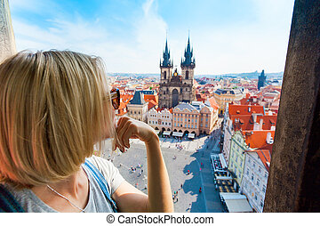 Young woman stands on top of clock tower and looks at Old...
