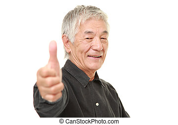 senior Japanese man with thumbs up gesture - studio shot of...
