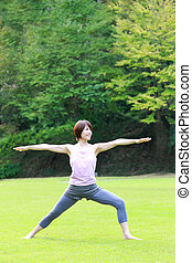 Japanese woman doing yoga warrior II pose - Portrait of...