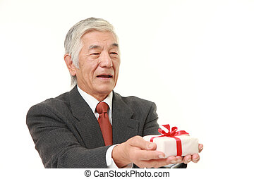 senior Japanese businessman offering a gift - portrait of...