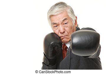 senior Japanese businessman throwing a left jab - portrait...