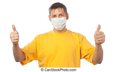 Young man in medical mask giving a thumbs up sign