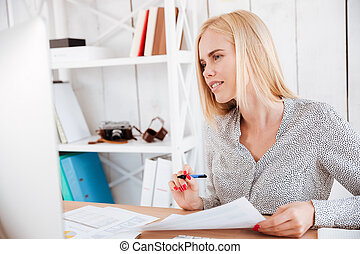 Casual young businesswoman making notes while looking at computer monitor