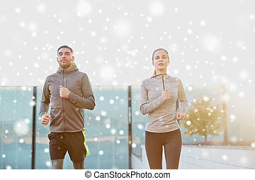 happy couple of sportsmen running in city - fitness, sport,...