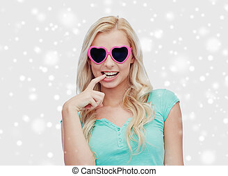 happy woman or teenager in heart shaped sunglasses -...