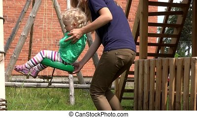 Mother pushing toddler daughter on swing in outdoor playground.