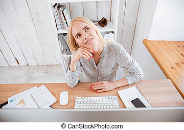 Business woman sitting at her workplace and thinking about...