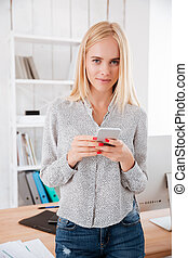 Businesswoman using mobile phone in office and looking at camera