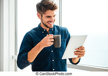Young happy man holding tablet and drinking coffee - Photo...