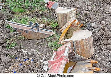 Arsenal of excavator's buckets on the ground, various sizes and shapes