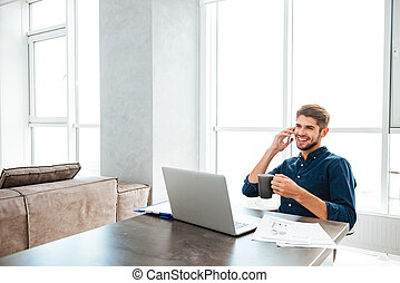 Young happy man talking on his phone and drinking coffee