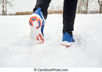close up of feet running along snowy winter road - fitness,...