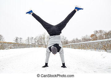 young man doing handstand in winter - fitness, sport,...