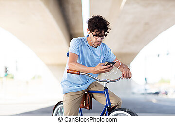 man with smartphone and earphones on bicycle - people,...