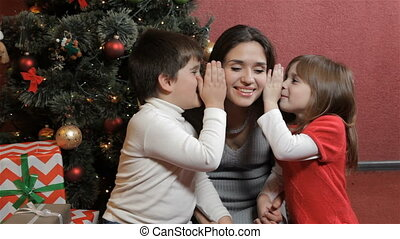 Two kids wisper into woman's ears near the christmas tree -...