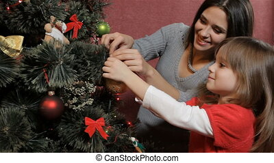 Mother helps her daughter to hang the bauble on the christmas tree