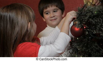 Little boy hangs decorating bow on christmas tree