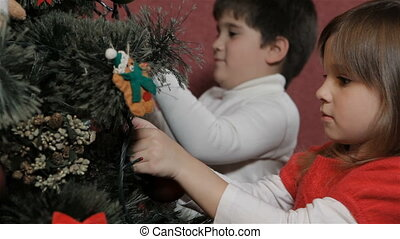 Children decorate the christmas tree - Two caucasian...