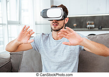 Young man wearing virtual reality device while sitting on...