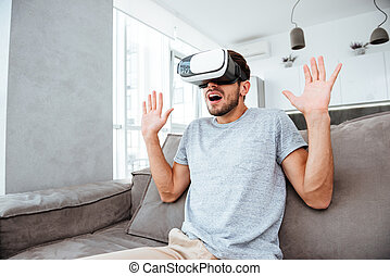 Confused young man wearing virtual reality device - Photo of...