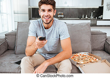 Man holding remote control and pushing the button - Photo of...