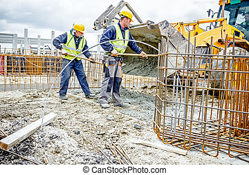 Workers are unloading concrete with shovel from excavator's...