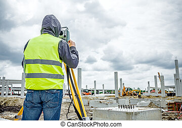 Geodesist is working with total station on a building site....