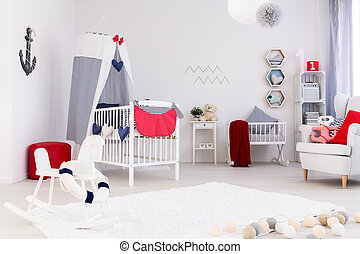 Bright room with crib and a rocking horse in nautical style