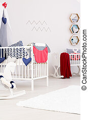 Crib and rocking horse in room - Crib with a red blanket and...