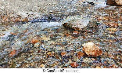 Clear water runs between the stones. Focus on the foreground. Valley Issyk-Ata, Kyrgyzstan