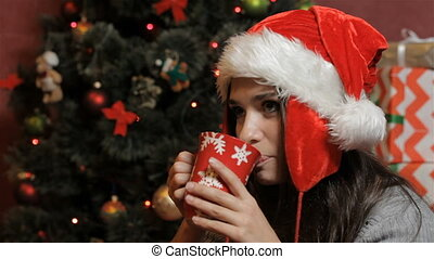 Woman in santa's hat drinking some beverage - Young...