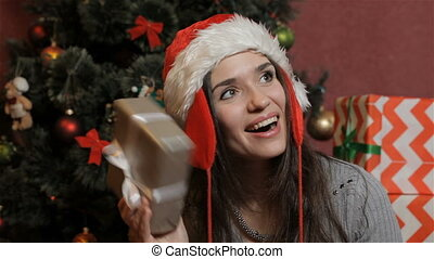 Woman shakes the christmas gift box - Attractive brunette...