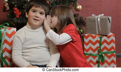 Kids share secrets near the christmas tree - Little...