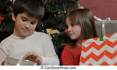 Kids look at their christmas gifts - Little kids looking at...