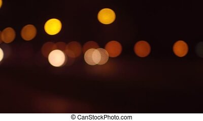 Street traffic bokeh circles at night. Cars passing by. 4K pan shot