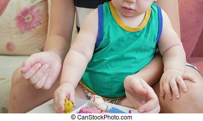 Beautiful baby boy sculpts the clay with his mother at home. Together having fun and making animal figurines. child education concept