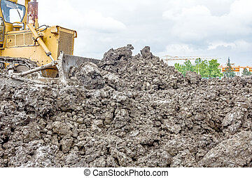 Heavy earthmover construction machine is moving earth at...