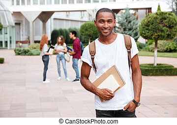 Smiling african man student with backpack standing outdoors
