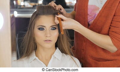 Professional hairdresser doing hairstyle for beautiful girl.