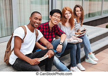 Cheerful young people sitting outdoors together