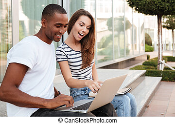 Happy couple talking and using laptop outdoors - Happy...