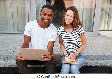 Smiling couple using laptop outdoors together - Smiling...