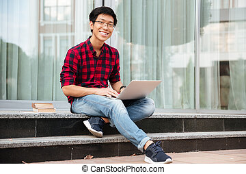 Happy asian young man using laptop outdoors - Happy asian...