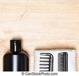 Hair care and styling background. Black bottle, wide tooth...