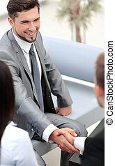 Happy smiling business man shaking hands after a deal in...