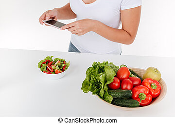 Cropped picture of lady photographing salad on phone