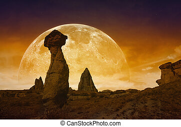 Rising bloody red full moon, silhouettes of mushroom rocks