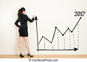 business woman drawing a graph on white wall background -...