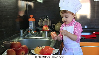 cute little baby dressed as a cook helps mum to cleans...