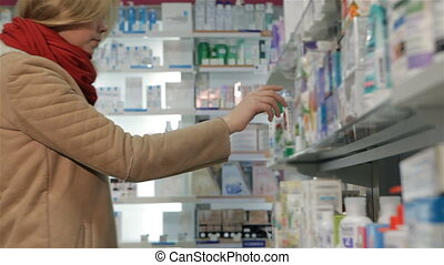 Female customer takes ointment from shelf at the drugstore -...